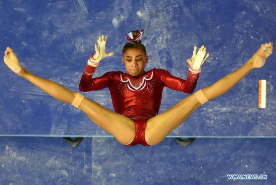 Ashton Locklear of USA performs on the uneven bars during the women's team final of the 45th Gymnastics World Championships in Nanning, capital of south China's Guangxi Zhuang Autonomous Region, Oct. 8, 2014. Team USA won the title with a total of 179.280 points. (Xinhua/Wang Yuguo)