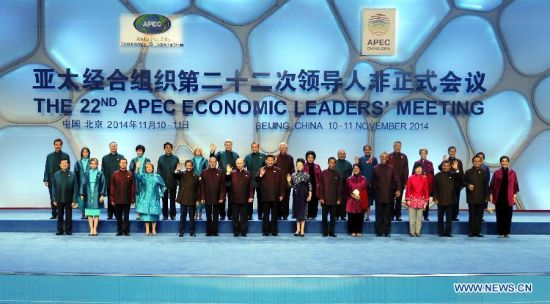 Chinese President Xi Jinping and his wife Peng Liyuan pose for a group photo with participants of the 22nd APEC Economic Leaders' Meeting and their spouses ahead of a welcome banquet in Beijing, capital of China, Nov. 10, 2014. (Xinhua/Ju Peng