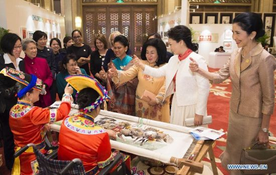 Peng Liyuan (2nd R), wife of Chinese President Xi Jinping, demonstrates to spouses of some leaders of the Asia-Pacific Economic Cooperation (APEC) member economies how to communicate with a deaf-mute girl by sign language during an activity focusing on development issues concerning disabled people, in Beijing, China, Nov. 10, 2014. (Xinhua/Huang Jingwen)