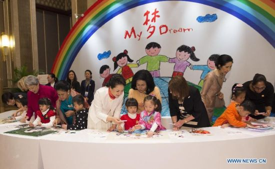 Peng Liyuan (in white dress), wife of Chinese President Xi Jinping, plays jigsaw puzzle with children with hearing impairment together with spouses of some leaders of the Asia-Pacific Economic Cooperation (APEC) member economies during an activity focusing on development issues concerning disabled people, in Beijing, China, Nov. 10, 2014. (Xinhua/Huang Jingwen)