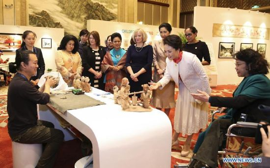 Peng Liyuan (in white dress), wife of Chinese President Xi Jinping, views the pottery created by deaf-mute artist Kang Zhimin together with spouses of some leaders of the Asia-Pacific Economic Cooperation (APEC) member economies during an activity focusing on development issues concerning disabled people, in Beijing, China, Nov. 10, 2014. (Xinhua/Huang Jingwen)