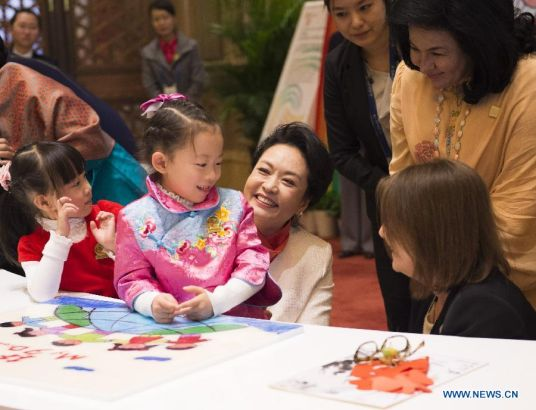 Peng Liyuan (C), wife of Chinese President Xi Jinping, reacts while playing jigsaw puzzle with children with hearing impairment together with spouses of some leaders of the Asia-Pacific Economic Cooperation (APEC) member economies during an activity focusing on development issues concerning disabled people in Beijing, China, Nov. 10, 2014. (Xinhua/Huang Jingwen)
