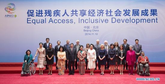 Peng Liyuan (6th R front), wife of Chinese President Xi Jinping, poses for a group photo with spouses of some leaders of the Asia-Pacific Economic Cooperation (APEC) member economies and guests after a meeting focusing on development issues concerning disabled people in Beijing, China, Nov. 10, 2014. (Xinhua/Ding Lin)