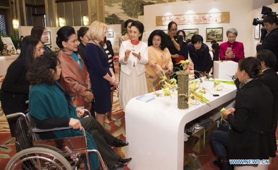 Peng Liyuan (in white dress), wife of Chinese President Xi Jinping, watch two blind artists make palm weavings while attending an activity focusing on development issues concerning disabled people along with spouses of some leaders of the Asia-Pacific Economic Cooperation (APEC) member economies, in Beijing, China, Nov. 10, 2014. (Xinhua/Ding Lin)