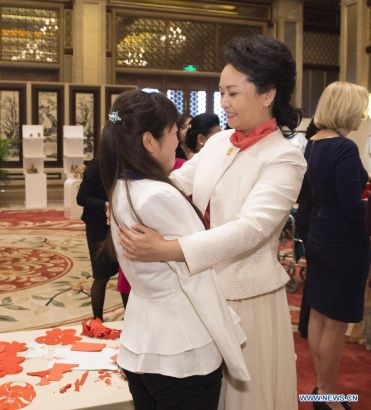 Peng Liyuan (R), wife of Chinese President Xi Jinping, embraces Xia Hong, a young woman who lost her arms, while attending an activity focusing on development issues concerning disabled people along with spouses of some leaders of the Asia-Pacific Economic Cooperation (APEC) member economies, in Beijing, China, Nov. 10, 2014. (Xinhua/Huang Jingwen)