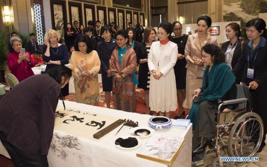 Peng Liyuan (in white dress), wife of Chinese President Xi Jinping, watch the performance by a disabled calligrapher while attending an activity focusing on development issues concerning disabled people along with spouses of some leaders of the Asia-Pacific Economic Cooperation (APEC) member economies, in Beijing, China, Nov. 10, 2014. (Xinhua/Ding Lin)