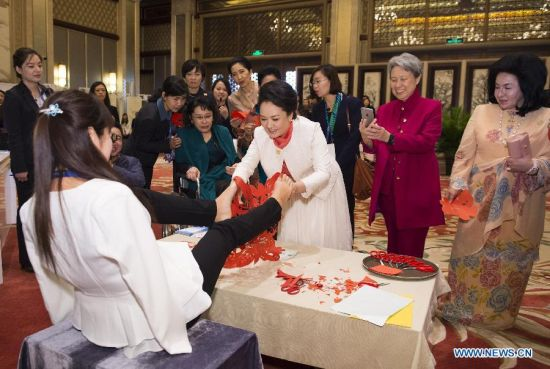Peng Liyuan (3rd R, front), wife of Chinese President Xi Jinping, receives a papercutting work created by Xia Hong, a young woman who lost her arms, as a present, while attending an activity focusing on development issues concerning disabled people along with spouses of some leaders of the Asia-Pacific Economic Cooperation (APEC) member economies in Beijing, China, Nov. 10, 2014. (Xinhua/Huang Jingwen)