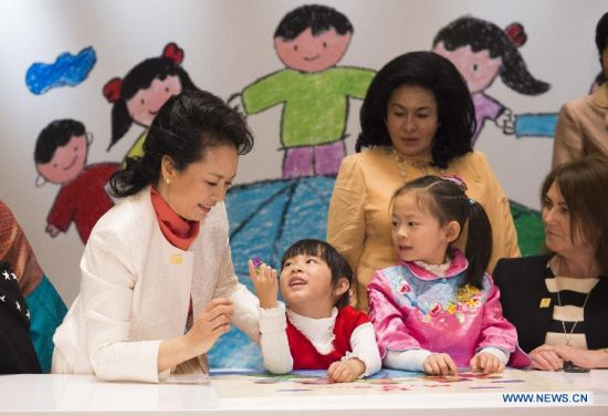 Peng Liyuan (L), wife of Chinese President Xi Jinping, receives a flower ring from a girl while playing jigsaw puzzle with children with hearing impairment together with spouses of some leaders of the Asia-Pacific Economic Cooperation (APEC) member economies during an activity focusing on development issues concerning disabled people in Beijing, China, Nov. 10, 2014.(Xinhua/Huang Jingwen)