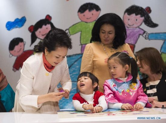 Peng Liyuan (L), wife of Chinese President Xi Jinping, receives and wears a flower ring from a girl while playing jigsaw puzzle with children with hearing impairment together with spouses of some leaders of the Asia-Pacific Economic Cooperation (APEC) member economies during an activity focusing on development issues concerning disabled people in Beijing, China, Nov. 10, 2014. (Xinhua/Huang Jingwen)