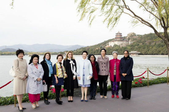 Chinese President Xi Jinping's wife Peng Liyuan, fifth right, hosted the wives of other APEC officials on a visit to the Summer Palace on the sidelines of the meeting. They are pictured on the bank of Kunming Lake in the largest and best preserved imperial garden of the Qing Dynasty in Beijing on Tuesday. [Photo/Xinhua]