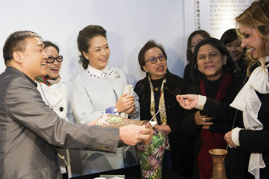 First lady Peng Liyuan helps her Mexican counterpart, Angelica Rivera, put the final touches on a traditional Chinese cloisonne vase during a tour of the Summer Palace in Beijing on Tuesday.[Photo/Xinhua]