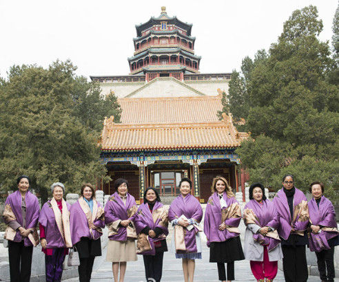 Peng, fifth right, and her guests pose for a group photo in front of the main buildings of the Summer Palace at the foot of Wanshou Mountain.[Photo/Xinhua]