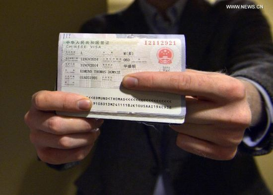 Edmund Thomas Downie shows his visa to the press after becoming the first American citizen to be issued a ten-year visa at the Visa Department of the Chinese Embassy to the United States in Washington D.C., Nov. 12, 2014. China issued the first-ever group of visas with ten-year validity to U.S. citizens here on Wednesday, implementing a new agreement that is expected to boost exchange between the two countries. (Xinhua/Yin Bogu)