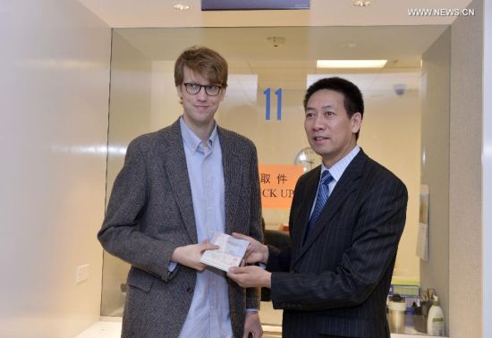 Edmund Thomas Downie (L) receives his long-term visa from Ruan Ping, Consul General at the Chinese Embassy in the U.S., at the Visa Department of the Chinese Embassy to the United States in Washington D.C., Nov. 12, 2014. China issued the first-ever group of visas with ten-year validity to U.S. citizens here on Wednesday, implementing a new agreement that is expected to boost exchange between the two countries. (Xinhua/Yin Bogu)