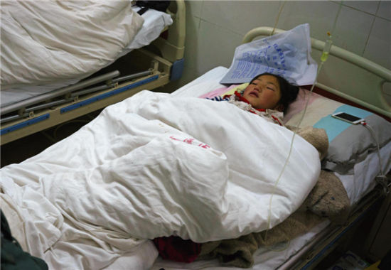 A girl from Kangding county receives treatment at the People's Hospital of Ganzi Tibetan autonomous prefecture in Southwest China's Sichuan province, Nov 23, 2014. [Photo/Xinhua]