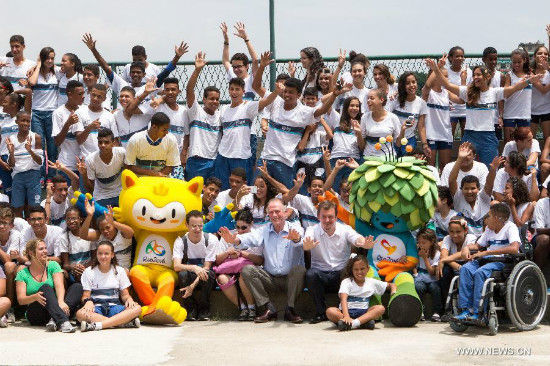 The mascot of Rio 2016 Olympic Games and Paralympic Games pose for a photo with young students in Rio de Janeiro, Brazil, Nov. 24, 2014. The unveiling ceremony of the mascots was held here on Monday. The mascot Rio 2016 Olympic and Paralympic was originated from the animals and plants in Brazil respectively. A poll to decide their names will be opened after the unveiling of the two mascots. (Xinhua/Xu Zijian)