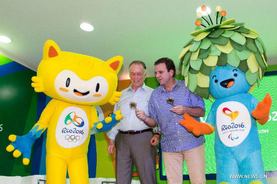 Eduardo Paes (2nd R), mayor of the city of Rio de Janeiro, presents the key of Rio de janeiro to the mascots in Rio de Janeiro, Brazil, Nov. 24, 2014. The unveiling ceremony of the mascots was held here on Monday. The mascot Rio 2016 Olympic and Paralympic was originated from the animals and plants in Brazil respectively. A poll to decide their names will be opened after the unveiling of the two mascots. (Xinhua/Xu Zijian)