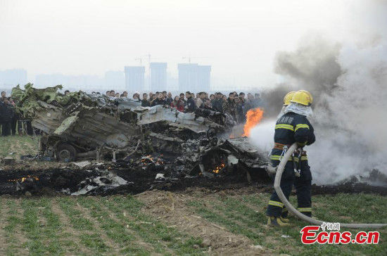 Rescuers try to put out the fire on the wreckage of an air force plane after it crashed in Northwest China's Shaanxi province on December 22, 2014. The plane had two on board when it crashed at 3:44 pm on the outskirts of Weinan city, according to rescuers. One of the pilots was pronounced dead on the spot, while the other died in hospital. Cause of the accident is being investigated. [Photo/ IC]