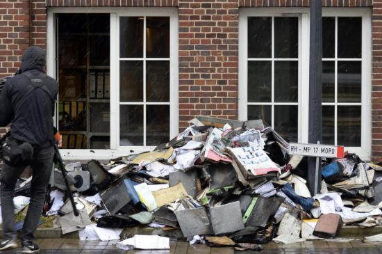 A member of a television crew is seen beside burned files and documents in front of a building of German newspaper Hamburger Morgenpost in Hamburg January 11, 2015. (REUTERS/Fabian Bimmer)
