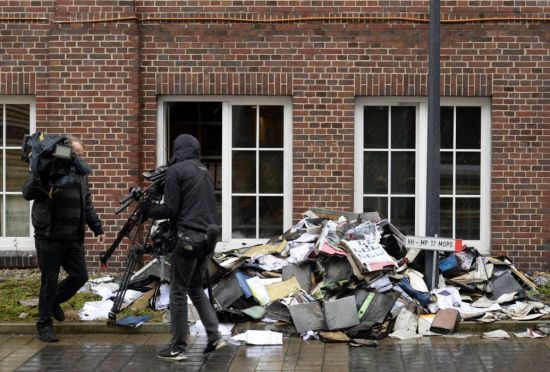Members of a television crew are seen beside burned files and documents in front of a building of German newspaper Hamburger Morgenpost in Hamburg January 11, 2015. (REUTERS/Fabian Bimmer)