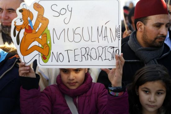 A girl holds a placard that reads