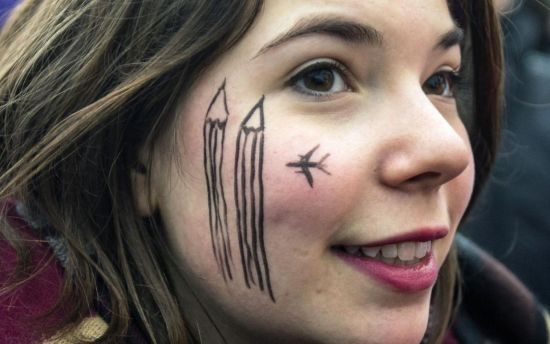 A woman wears a cartoon painting on the face during a silent protest for the victims of the shooting at the Paris offices of weekly newspaper Charlie Hebdo, at the Pariser Platz square in Berlin January 11, 2015. (REUTERS/Hannibal Hanschke)