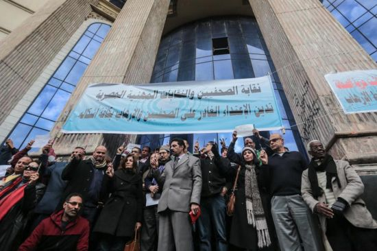 Head of the Egyptian Press Syndicate Diaa Rashwan holds a pen in a show of solidarity with the victims of Wednesday's attack in Paris on the Charlie Hebdo newspaper, at the Press Syndicate in Cairo, Egypt, Sunday, Jan. 11, 2015. The attack on the French satirical newspaper has caused grief and soul-searching around the world, and exposed the risks humorists can run in an era of instant global communications and starkly opposed ideologies. Despite the show of solidarity, some fear the violence will lead to self-censorship by artists and publishers. (AP Photo/Mosa'ab Elshamy)