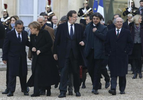 Carla Bruni-Sarkozy, back left, former French President Nicolas Sarkozy, second from left, German Chancellor Angela Merkel, third from left, Spanish Prime Minister Mariano Rajoy, center, and Danish Prime Minister Helle Thorning-Schmidt, back far right, leave the Elysee Palace to board a bus to join a rally, Paris, Sunday, Jan. 11, 2015. A rally of defiance and sorrow, protected by an unparalleled level of security, on Sunday will honor the 17 victims of three days of bloodshed in Paris that left France on alert for more violence. (AP Photo/Thibault Camus)