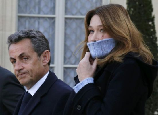 Former French President Nicolas Sarkozy (L), head of the French conservative party UMP party, and his wife Carla Bruni-Sarkozy (R) arrive at the Elysee Palace before attending a solidarity march (Marche Republicaine) in the streets of Paris January 11, 2015. Hundreds of thousands of French citizens will be joined by dozens of foreign leaders, among them Arab and Muslim representatives, in a march on Sunday in an unprecedented tribute to this week's victims following the shootings by gunmen at the offices of the satirical weekly newspaper Charlie Hebdo, the killing of a police woman in Montrouge, and the hostage taking at a kosher supermarket at the Porte de Vincennes. (REUTERS/Philippe Wojazer)
