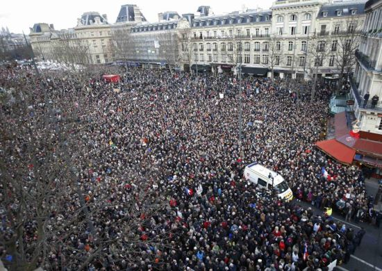 A general view shows an ambulance surrounded by hundreds of thousands of people gathering on the Place de la Republique to attend the solidarity march (Rassemblement Republicain) in the streets of Paris January 11, 2015. French citizens will be joined by dozens of foreign leaders, among them Arab and Muslim representatives, in a march on Sunday in an unprecedented tribute to this week's victims following the shootings by gunmen at the offices of the satirical weekly newspaper Charlie Hebdo, the killing of a police woman in Montrouge, and the hostage taking at a kosher supermarket at the Porte de Vincennes. (REUTERS/Charles Platiau)