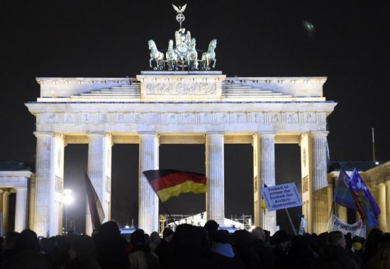 People with German national flags attend a BEGIDA rally near the Brandenburg Gate in Berlin on January 12, 2015 (AFP Photo/Tobias Schwarz)