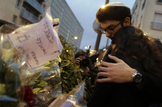 Mourners stand in front of flowers during a gathering at the end of Shabbat called by the Jewish Student's Union of France (UEJF) association on January 10, 2015, at the Porte de Vincennes in eastern Paris (AFP Photo/Kenzo Tribouillard)