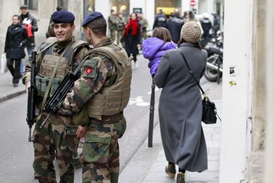 French army soldiers patrol near Rue des Rosiers street, in the heart of the Paris Jewish quarter, Monday Jan. 12, 2015. France on Monday ordered 10,000 troops into the streets to protect sensitive sites after three days of bloodshed and terror, amid the hunt for accomplices to the attacks that left 17 people and the three gunmen dead. (AP Photo/Remy de la Mauviniere)