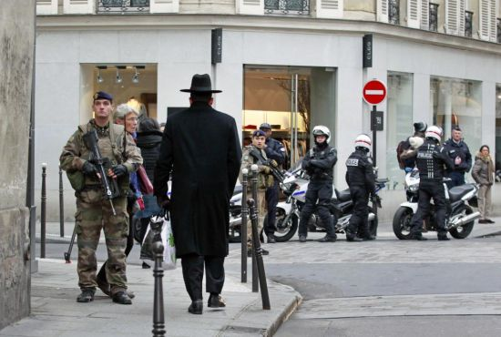 Police officers and French army soldiers patrol Rue des Rosiers street, in the heart of Paris Jewish quarter, in Paris, Monday Jan. 12, 2015. France on Monday ordered 10,000 troops into the streets to protect sensitive sites after three days of bloodshed and terror, amid the hunt for accomplices to the attacks that left 17 people and the three gunmen dead. (AP Photo/Remy de la Mauviniere)