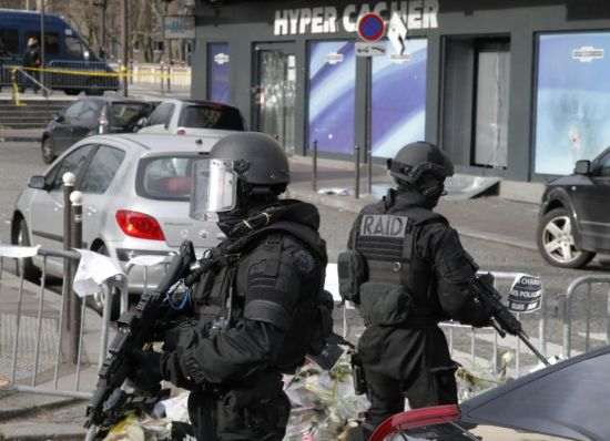 Elite police officers take position outside the kosher market where four hostages were killed and shortly before Israeli Prime Minister Benjamin Netanyahu's visit to the site, in Paris, France, Monday, Jan. 12, 2015. France's defense minister says the country is mobilizing 10,000 security forces to protect the country after three days of terror attacks. French Interior Minister Bernard Cazeneuve said 4,700 security forces would be assigned to protect France's 717 Jewish schools. (AP Photo/Francois Mori)