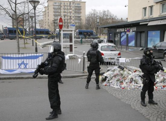 Elite police officers take position outside the kosher market where four hostages were killed, shortly before Israeli Prime Minister Benjamin Netanyahu's visit to the site, in Paris, France, Monday, Jan. 12, 2015. France's defense minister says the country is mobilizing 10,000 security forces to protect the country after three days of terror attacks. French Interior Minister Bernard Cazeneuve said 4,700 security forces would be assigned to protect France's 717 Jewish schools. (AP Photo/Francois Mori)
