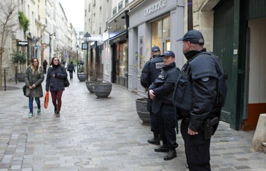Police officers patrol Rue des Rosiers street, in the heart of the Paris Jewish quarter, Monday Jan. 12, 2015. France on Monday ordered 10,000 troops into the streets to protect sensitive sites after three days of bloodshed and terror, amid the hunt for accomplices to the attacks that left 17 people and the three gunmen dead. (AP Photo/Remy de la Mauviniere)