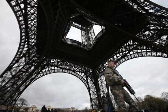 A French soldier patrols near the Eiffel Tower in Paris as part of the highest level of