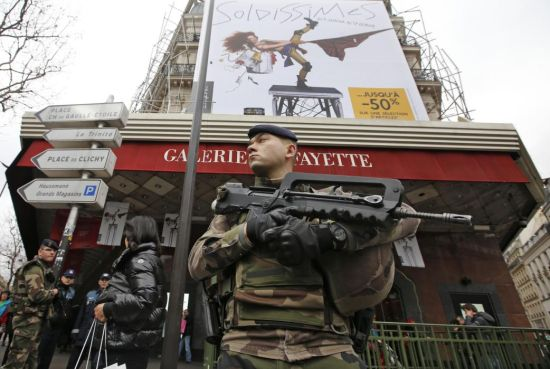 French soldiers patrol near a department store in Paris as part of the highest level of