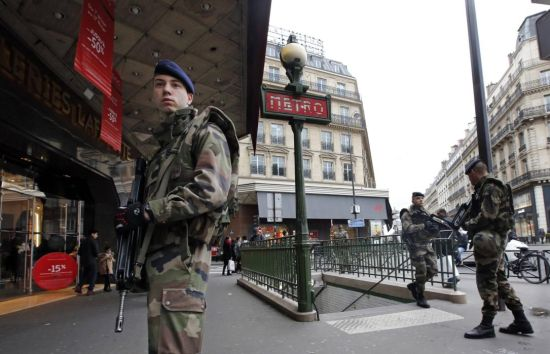 French soldiers patrol in the street near a department store in Paris as part of the highest level of