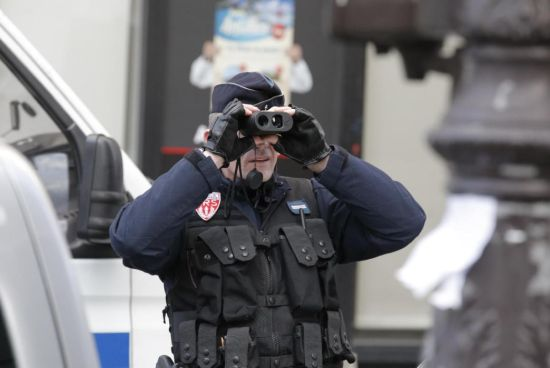 A police officer uses his binoculars near Republique Square in Paris before the start of a demonstration, Sunday, Jan. 11, 2015. A rally of defiance and sorrow, protected by an unparalleled level of security, on Sunday will honor the 17 victims of three days of bloodshed in Paris that left France on alert for more violence. (AP Photo/Francois Mori)