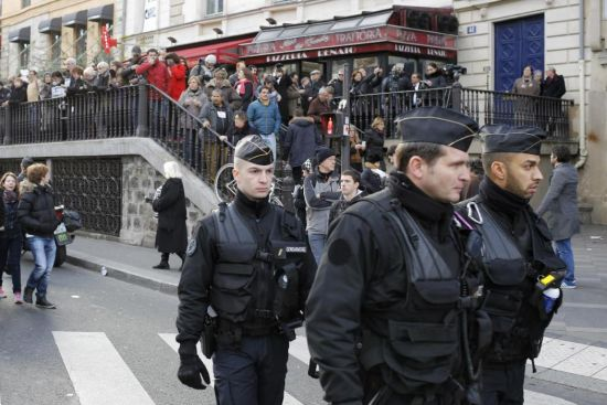Police officers patrol near Republique square before the demonstration, in Paris, France, Sunday, Jan. 11, 2015. A rally of defiance and sorrow, protected by an unparalleled level of security, on Sunday will honor the 17 victims of three days of bloodshed in Paris that left France on alert for more violence. (AP Photo/Laurent Cipriani)