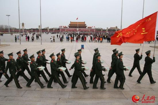 Arm police soldiers marched with pans and rags on Tian'anmen square.
