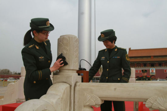 """Two female Armed Policewomen clean a marble post near the Chinese national flag in Beijing's Tian'anmen Square yesterday. Sheand more than 200 fellow officers were mobilized to clean guard rails in preparation forthe opening of the """"Two Sessions.""""More than3,500 lawmakers and 2,000 political advisers willmeet at the Great Hall of the People from March 3 to 15. — CFP"""