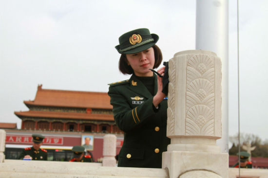 """A female Armed Policewoman cleans a marble post near the Chinese national flag in Beijing's Tian'anmen Square yesterday. Sheand more than 200 fellow officers were mobilized to clean guard rails in preparation forthe opening of the """"Two Sessions.""""More than3,500 lawmakers and 2,000 political advisers willmeet at the Great Hall of the People from March 3 to 15. — CFP"""