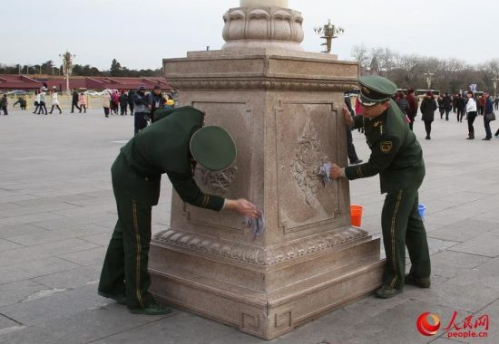 Solders clean the foundation of a lamp post on Tian'anmen Square.