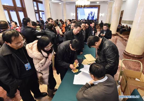 Registered journalists take their media badges ahead of the third session of the 12th Chinese People's Political Consultative Conference (CPPCC) in Beijing, capital of China, March 1, 2015. The session will open on March 3. (Xinhua/Li He)