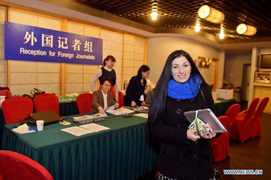 A journalist from Russia's RIA Novosti gets her press card at the reception desk in Beijing, China, March 1, 2015. Foreign journalists reporting the third session of the 12th National People's Congress (NPC) and the third session of the 12th Chinese People's Political Consultative Conference (CPPCC) began to register on Sunday at the Media Center Hotel in Beijing. (Xinhua/Li Xin)