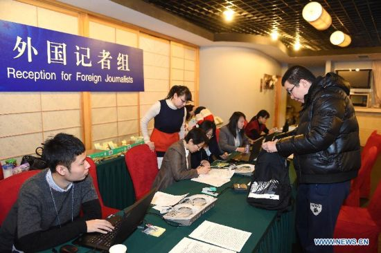 A Chinese employee (R) of Germany's ARD Fernsehen registers at the reception desk in Beijing, China, March 1, 2015. Foreign journalists reporting the third session of the 12th National People's Congress (NPC) and the third session of the 12th Chinese People's Political Consultative Conference (CPPCC) began to register on Sunday at the Media Center Hotel in Beijing. (Xinhua/Li Xin)