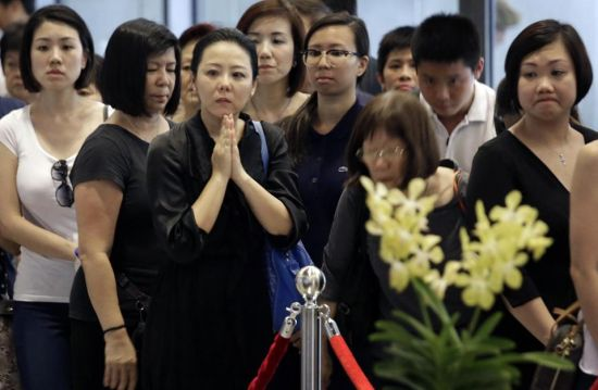 Members of the public pay their respects to the late Lee Kuan Yew at the Parliament House where he will lie in state for four days, Thursday, March 26, 2015, in Singapore. Lee, 91, died Monday at Singapore General Hospital after more than a month of battling severe pneumonia. The government declared a week of mourning for the leader who is credited with transforming the resource-poor island into a wealthy finance and trade hub with low crime and corruption in a region saddled with graft, instability and poverty. (AP Photo/Wong Maye-E)